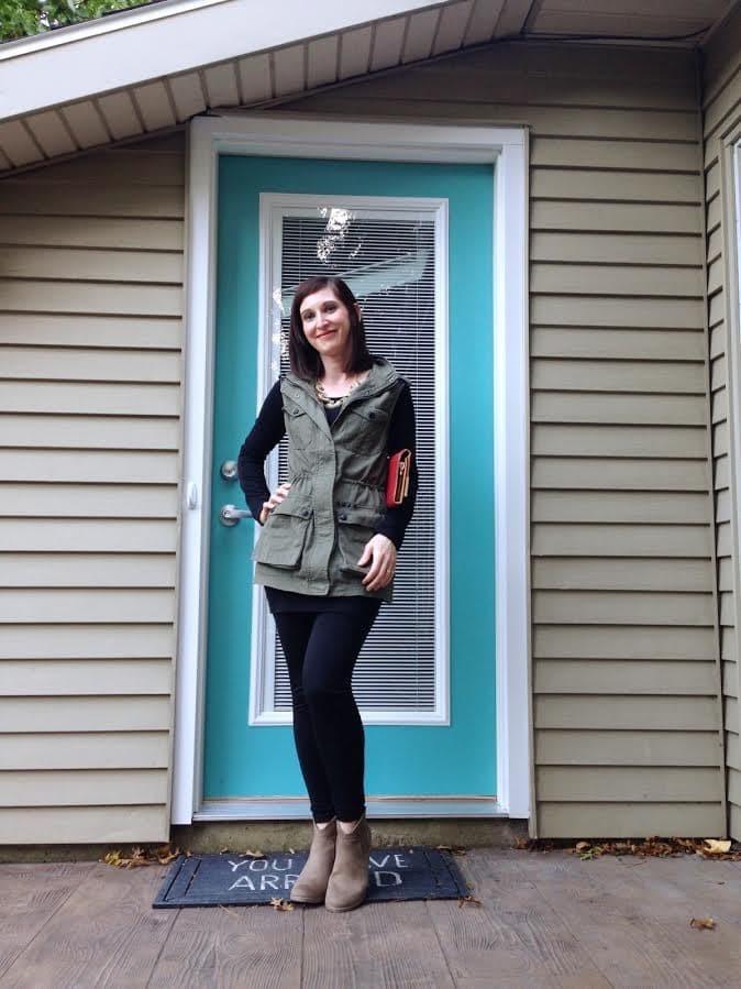 utility vest + statement necklace + black tunic + black leggings + booties