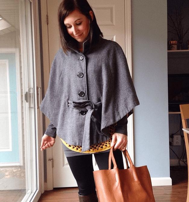 cape + black leggings + boots + camel purse