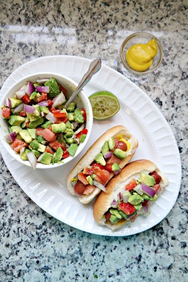 Grilled hot dogs with avocado relish via Dine & Dish