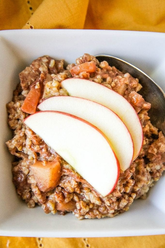 Overnight Slow Cooker Apple Cinnamon Steel Cut Oatmeal With Sliced Apples On Top