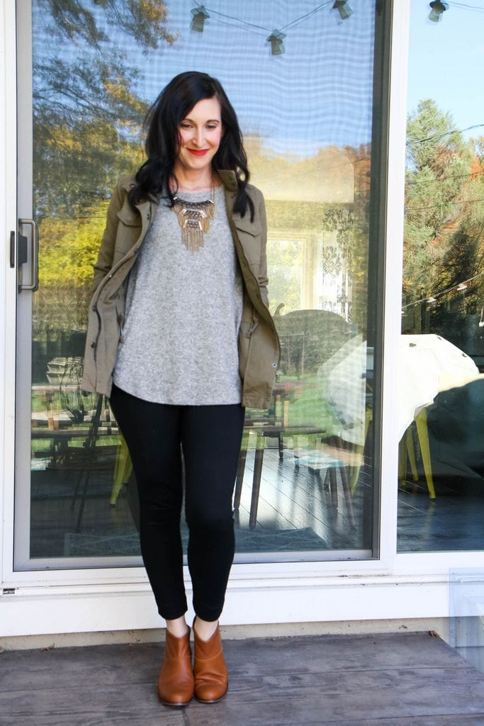 military jacket + gray shirt + statement necklace + black leggings + tan booties